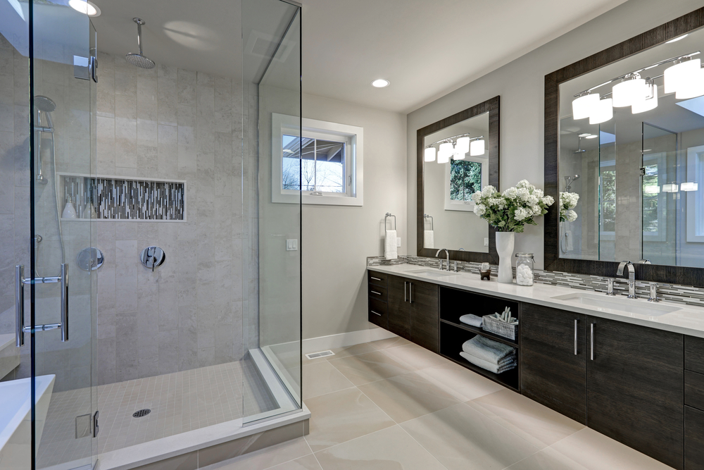 Spacious bathroom in gray tones with heated floors, walk-in shower, double sink vanity and skylights